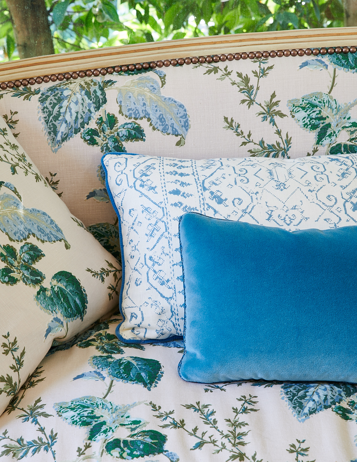 Leafy fabric upholstery on bench with metal studs and velvet throw pillow