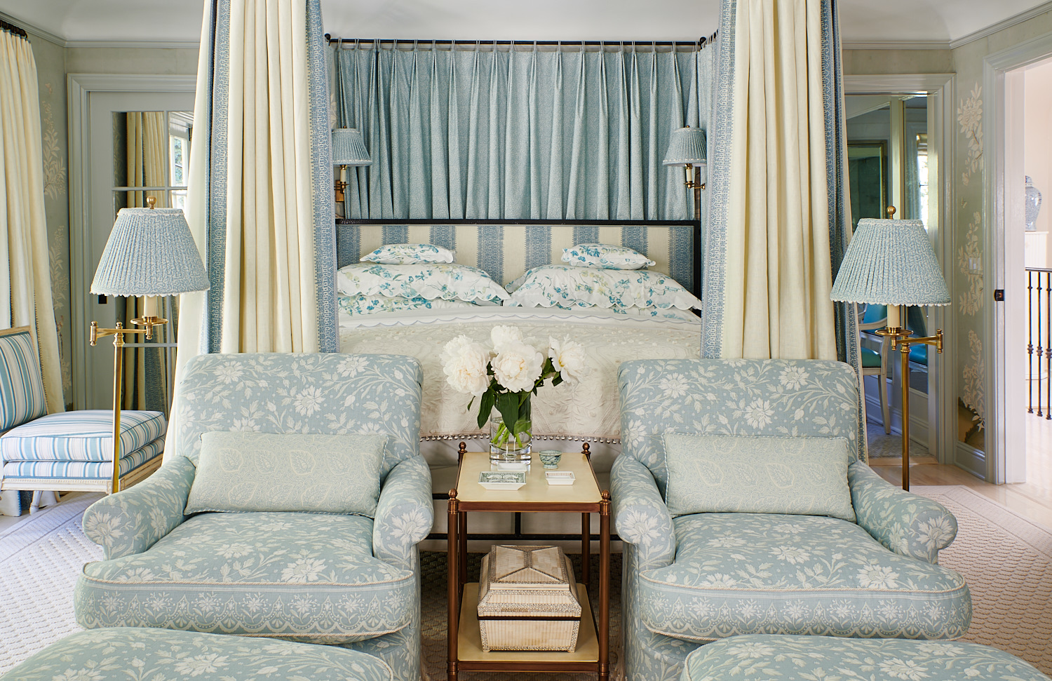 Wide view of bed drapes, stripe upholstered headboard, floral shams, and floral upholstered club chairs with matching ottomans
