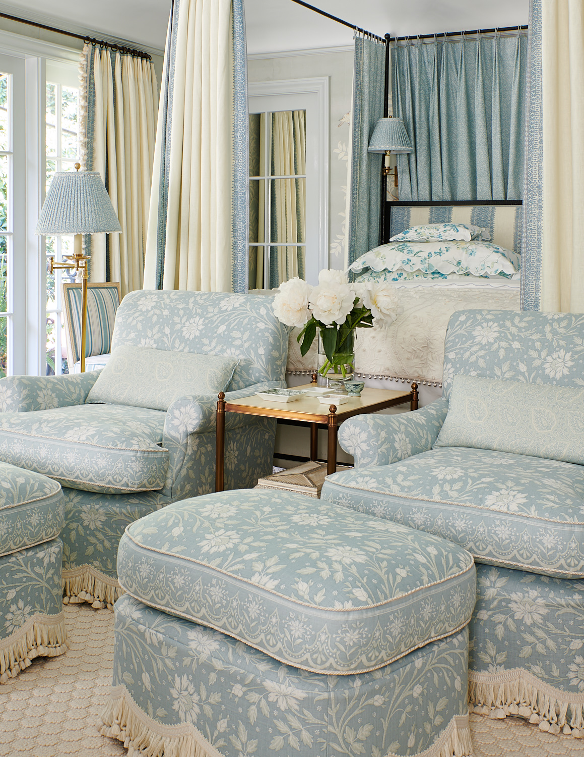 Dual floral upholstered club chairs with matching ottomans