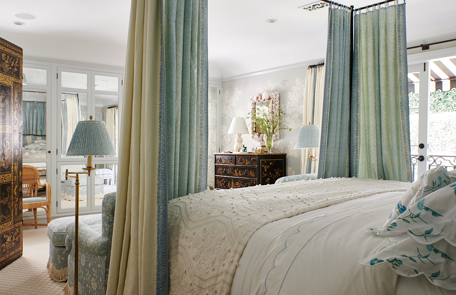 Custom bed drapes, floral pillow shams, floral upholstered club chair with accompanying ottoman